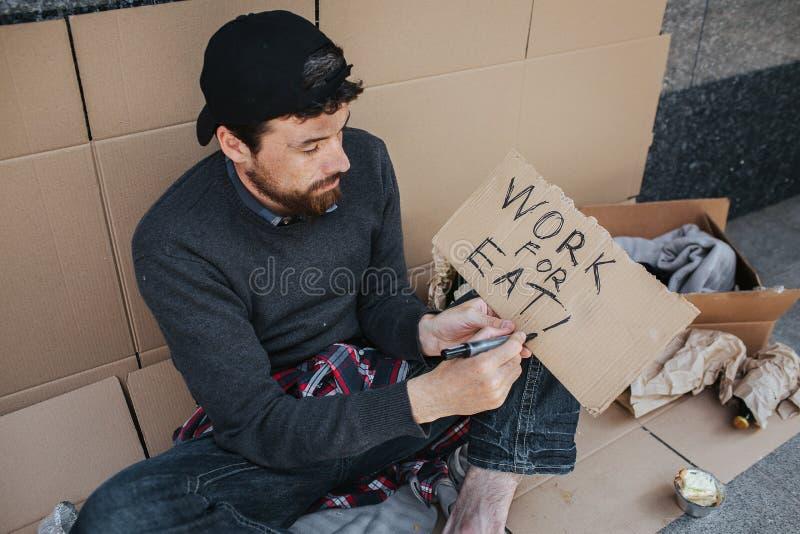 O homem desempregado está sentando-se na terra e escrevendo para baixo as palavras trabalham para comem no pedaço de papel O indi imagens de stock royalty free