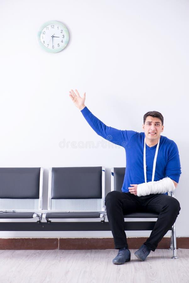 O homem desesperado que espera sua nomeação no hospital com quebrou fotografia de stock royalty free