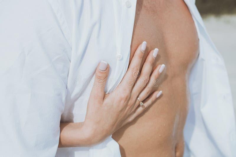 O homem despido muscular 'sexy' e as mãos fêmeas desafivelam suas calças de brim imagem de stock royalty free