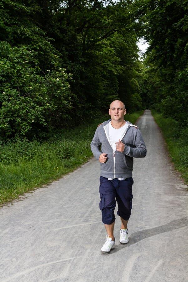 O homem desportivo está movimentando-se na floresta fotografia de stock