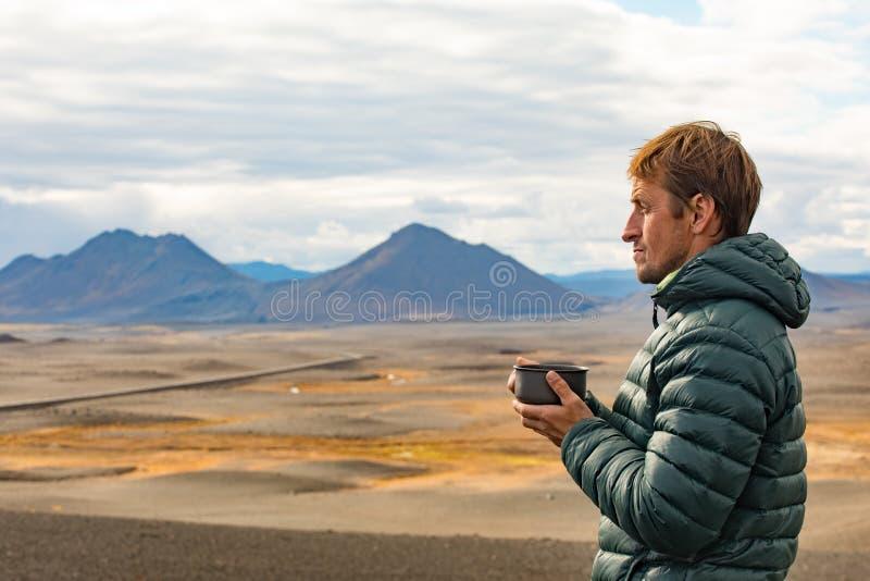 O homem do AA admira a paisagem com uma caneca de bebida quente Dia ensolarado do verão na natureza com uma paisagem bonita da mo imagem de stock royalty free