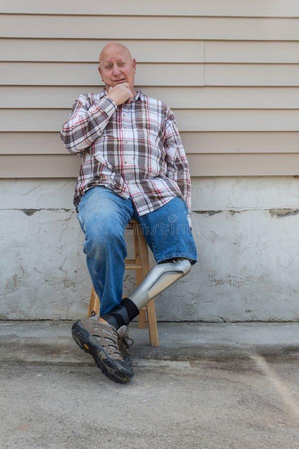 O homem do amputado que senta-se com pé protético cruzou-se, mão no queixo fotos de stock royalty free