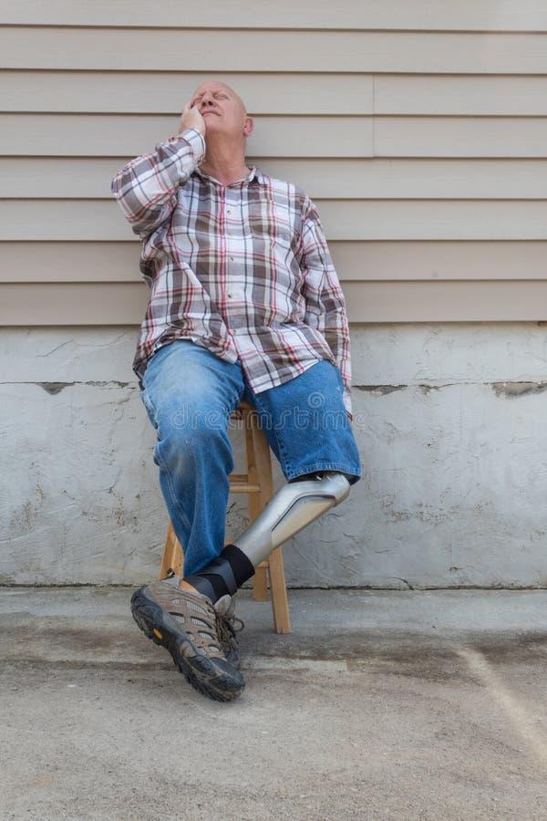 O homem do amputado que senta-se no tamborete com pé protético cruzou-se, olhando acima com mão ao lado da cara imagem de stock