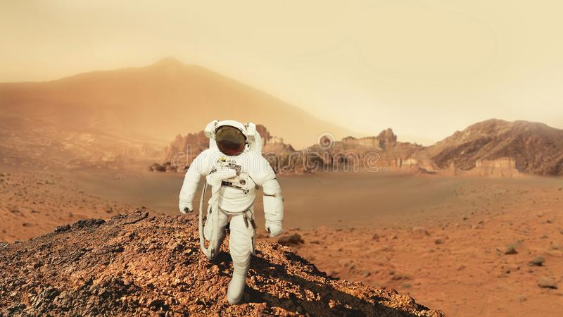 O homem do astronauta anda no deserto com as montanhas em Marte fotografia de stock royalty free