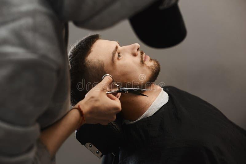 O homem do barbeiro apara a barba à moda do homem brutal novo considerável com corte de cabelo elegante que se senta na poltrona  foto de stock royalty free