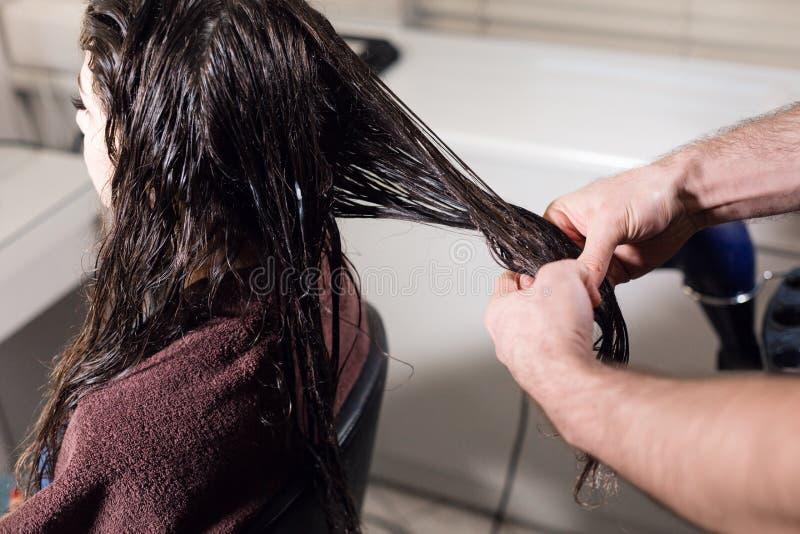 O homem do cabeleireiro do close up faz o penteado para a jovem mulher no salão de beleza fotos de stock