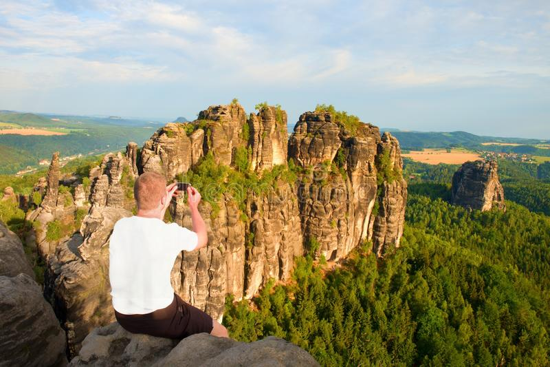 O homem do cabelo curto no penhasco da rocha e toma a foto pelo telefone esperto do fole da paisagem Dia ensolarado em montanhas  imagens de stock