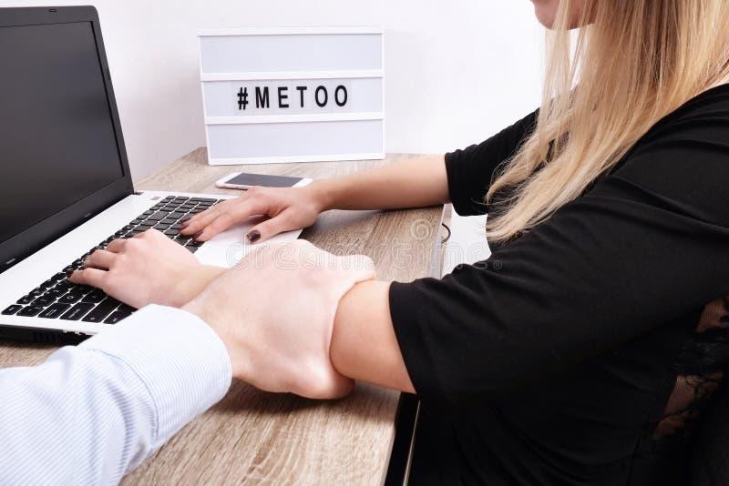 O homem do chefe mostra o comportamento impróprio para a jovem mulher na mesa do local de trabalho As garras masculinas violentas imagens de stock royalty free