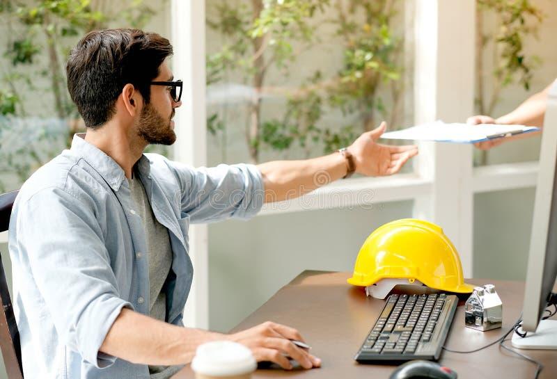 O homem do coordenador recebe o documento do colega de trabalho e senta-se na frente do computador na mesa no escritório da janel fotografia de stock