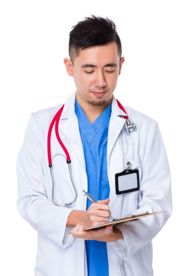 O homem do doutor escreve na prancheta fotografia de stock