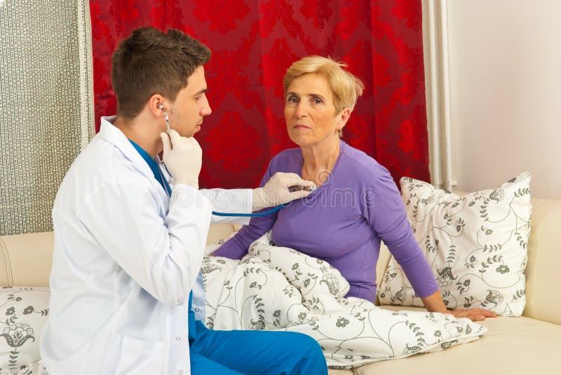 O homem do doutor examina a HOME sênior da mulher foto de stock