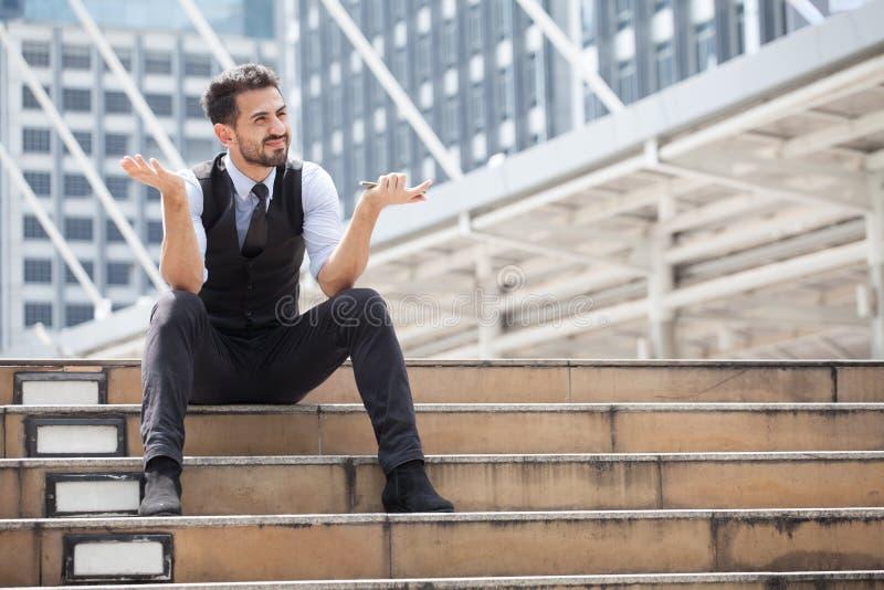 O homem do esforço que senta-se apenas na escada exterior O grito novo do homem de negócio abandonado perdeu na depressão com tel foto de stock royalty free