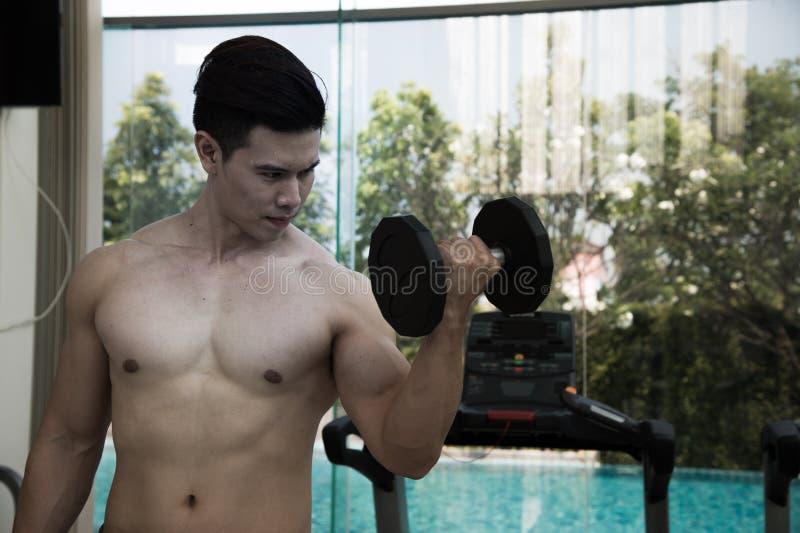 O homem do esporte está dando certo com o peso, exercitando dar certo no gym imagens de stock