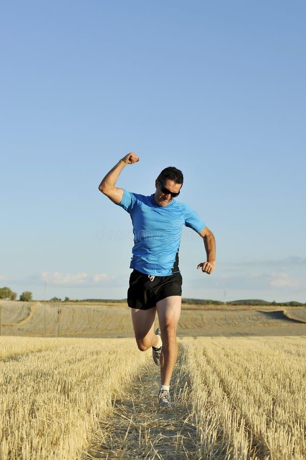 O homem do esporte que corre fora no campo da palha que faz a vitória assina dentro a perspectiva frontal foto de stock