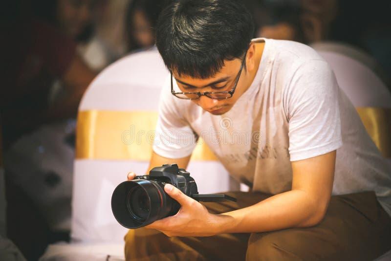 O homem do fabricante do fotógrafo e do vídeo guarda a câmera de DSLR em sua mão a fazer a metragem fotos de stock royalty free