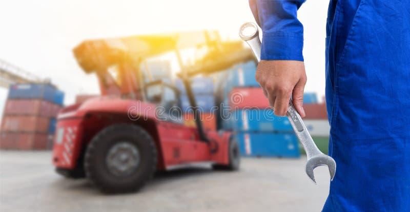 O homem do mecânico que guarda a chave com a empilhadeira no recipiente y imagens de stock