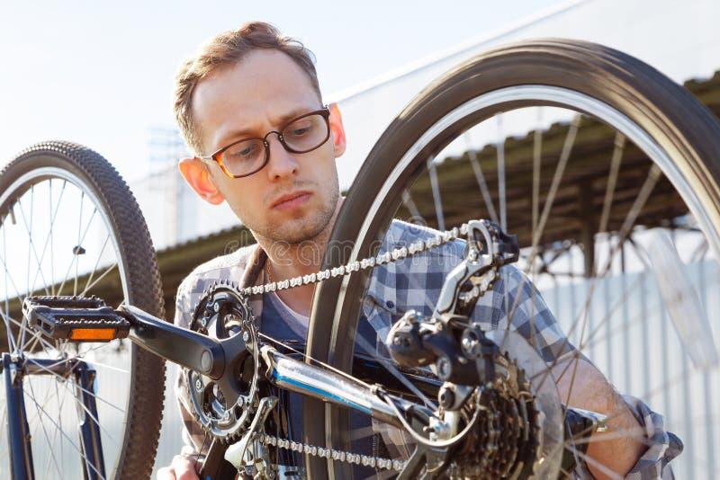 O homem do mecânico verifica o sistema de transmissão da bicicleta exterior imagens de stock