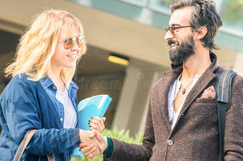 O homem do moderno e o aperto de mão louro da mulher no negócio informal datam imagens de stock royalty free