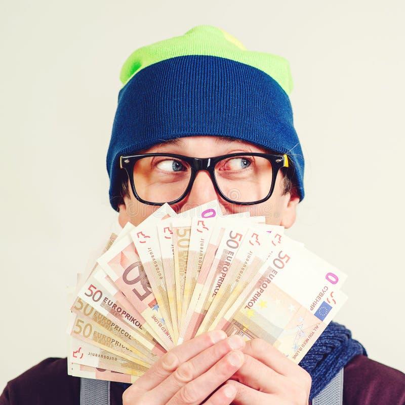 O homem do moderno nos vidros cobriu a cara com o dinheiro, olhando de lado Indivíduo no chapéu que tem o fã do dinheiro à dispos imagens de stock royalty free