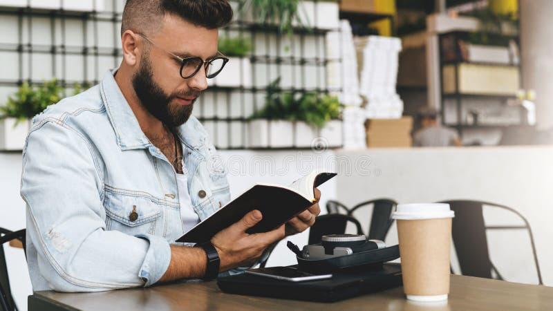 O homem do moderno nos vidros está sentando-se no café, lendo notas no caderno Na tabela é o portátil, xícara de café, câmera ins foto de stock