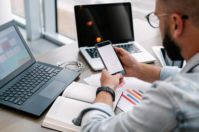 O homem do moderno senta-se no café, usa o smartphone, trabalha em dois portáteis O homem de negócios lê uma mensagem de informaç imagem de stock royalty free