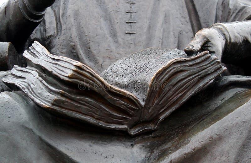 O homem do monumento guarda um livro aberto fotos de stock royalty free