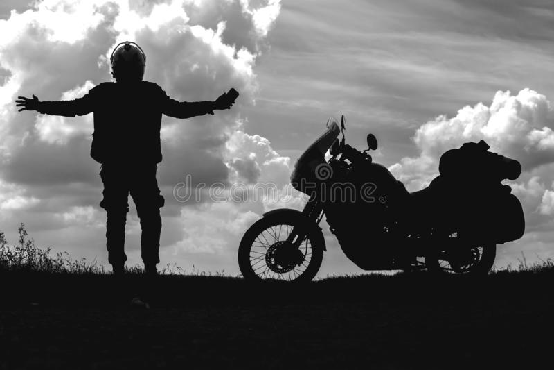 O homem do motociclista aprecia o momment e o turista fora da motocicleta da estrada com sacos laterais cavaleiro a descansar dur imagens de stock royalty free