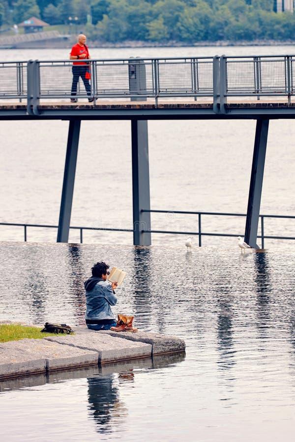 O homem do Oriente Médio novo lê um livro que senta-se pelo rio Decolou suas botas e seus pés estão na água fotos de stock royalty free