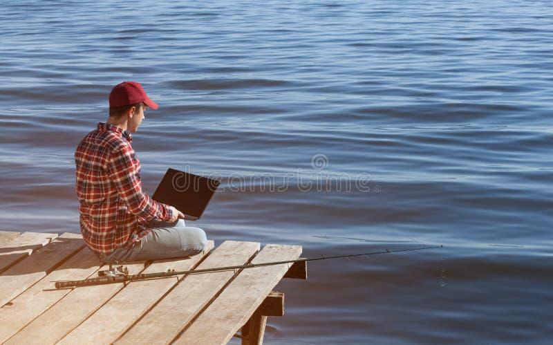 O homem do pescador trabalha em um portátil, senta-se em um cais de madeira perto do lago, ao lado dele lá é um polo de pesca imagens de stock
