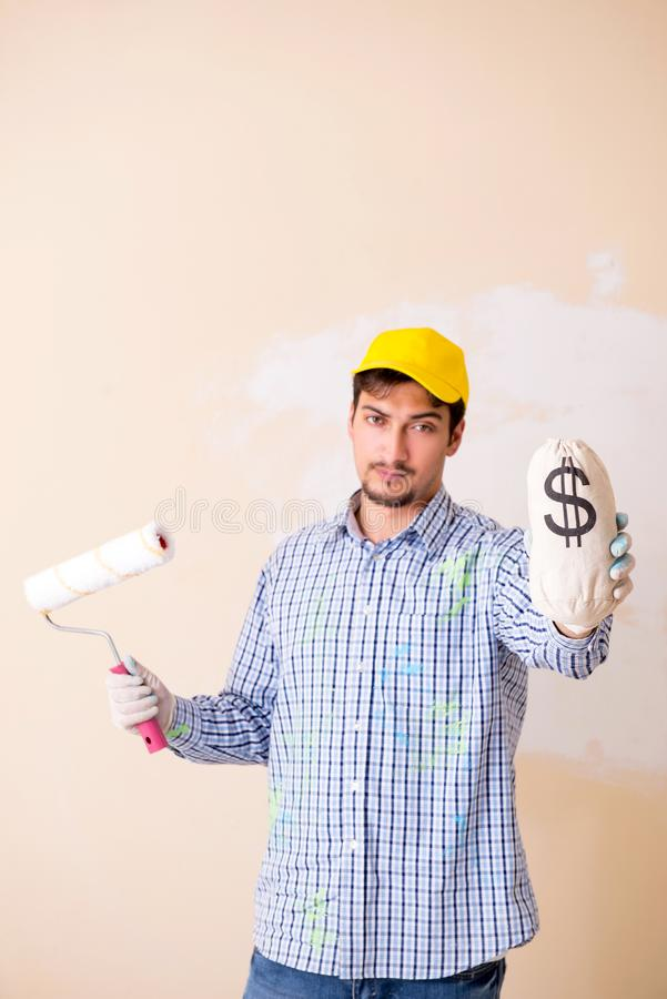 O homem do pintor que pinta a parede em casa imagem de stock royalty free
