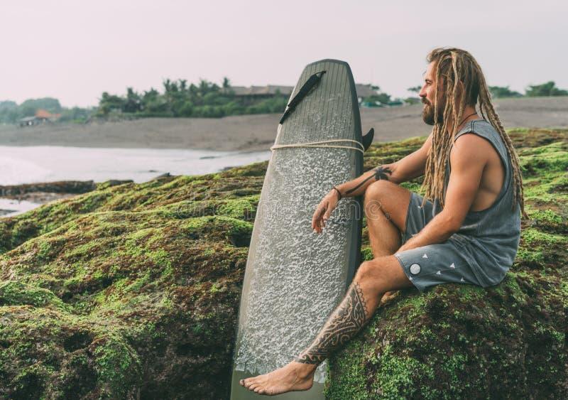 O homem do surfista com dreadlocks, tatuagens aproxima o oceano fotografia de stock