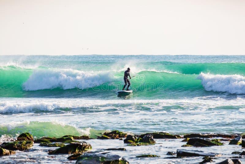 O homem do surfista levanta-se sobre a placa de pá na onda azul inverno que surfa no oceano fotografia de stock royalty free