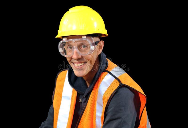O homem do trabalhador da construção no chapéu de segurança amarelo, veste alaranjada, luvas vermelhas, googles e preparando-se p foto de stock