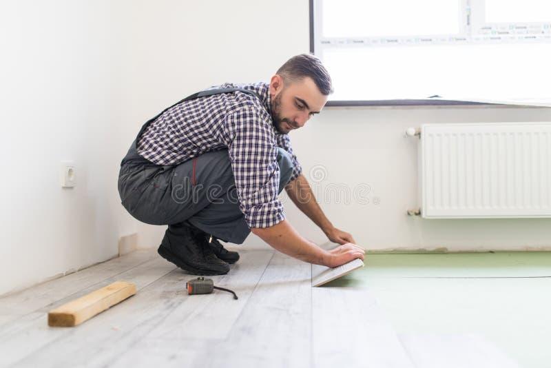 O homem do trabalhador está reparando o assoalho na casa, revestimento estratificado ao estilo das placas idosas fotografia de stock