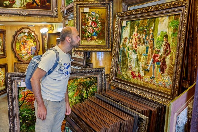 O homem do turista escolhe a lembrança em uma loja da arte, Isfahan, Irã imagens de stock