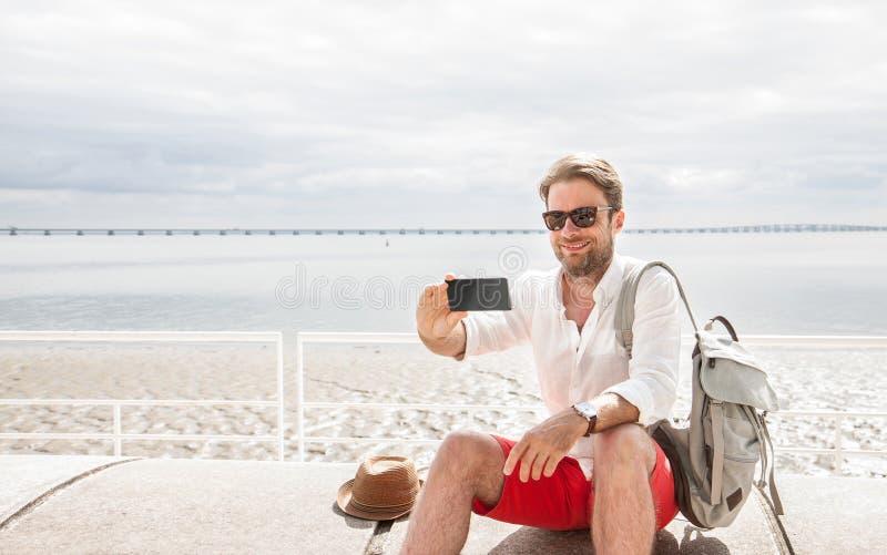 O homem do turista toma a uma foto dsi mesmo o selfie com smartphone do telefone imagens de stock