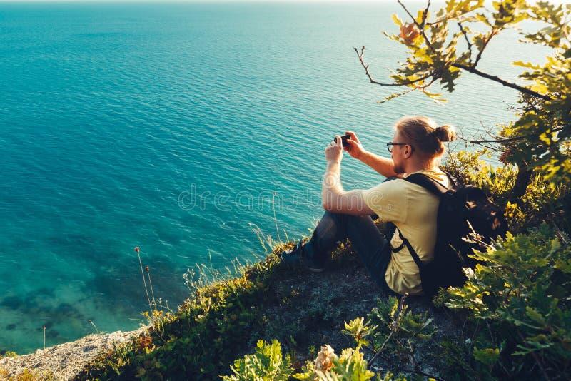 O homem do viajante senta-se na costa e toma-se imagens do mar na câmera do telefone celular durante o por do sol imagens de stock royalty free