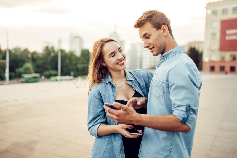 O homem do viciado do telefone mostra sua p?gina social ? mulher foto de stock royalty free