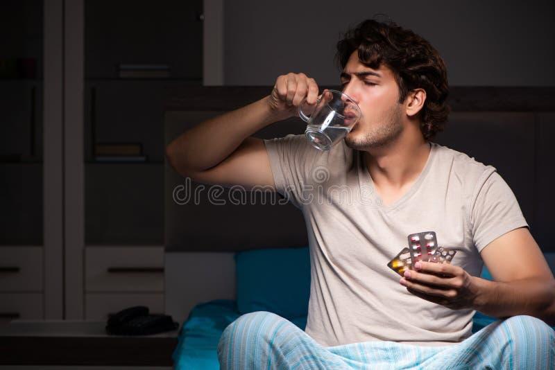 O homem doente em sua cama com medicinas imagem de stock royalty free