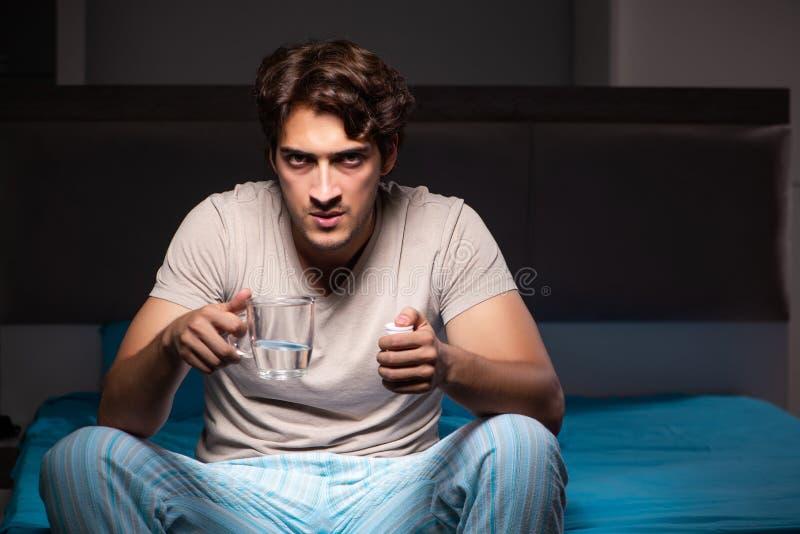 O homem doente em sua cama com medicinas fotos de stock royalty free