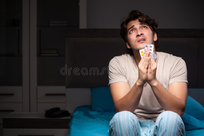 O homem doente em sua cama com medicinas fotografia de stock