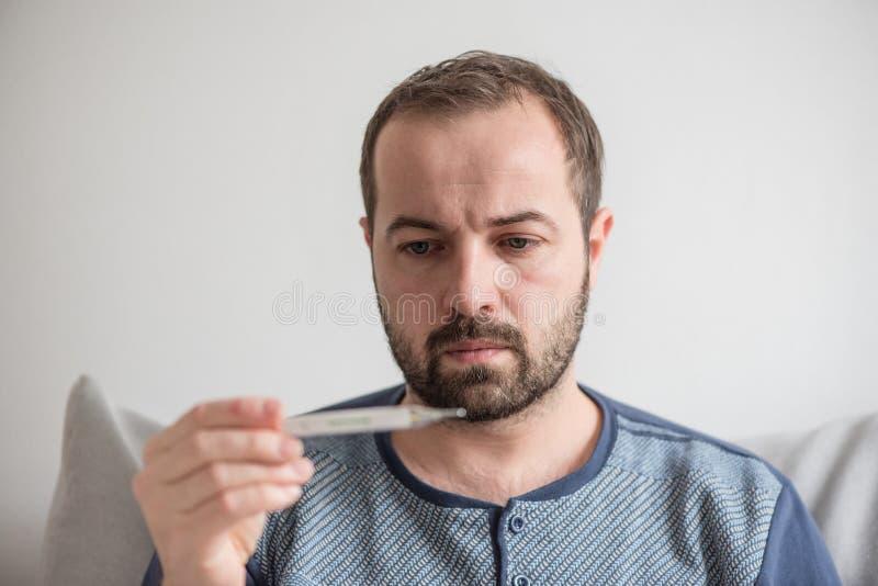 O homem doente verifica a temperatura corporal com um termômetro de mercúrio Tema de doenças virais, gripe, frios imagem de stock royalty free
