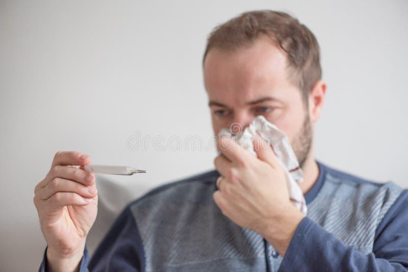 O homem doente verifica a temperatura corporal com um termômetro de mercúrio Tema de doenças virais, gripe, frios imagens de stock