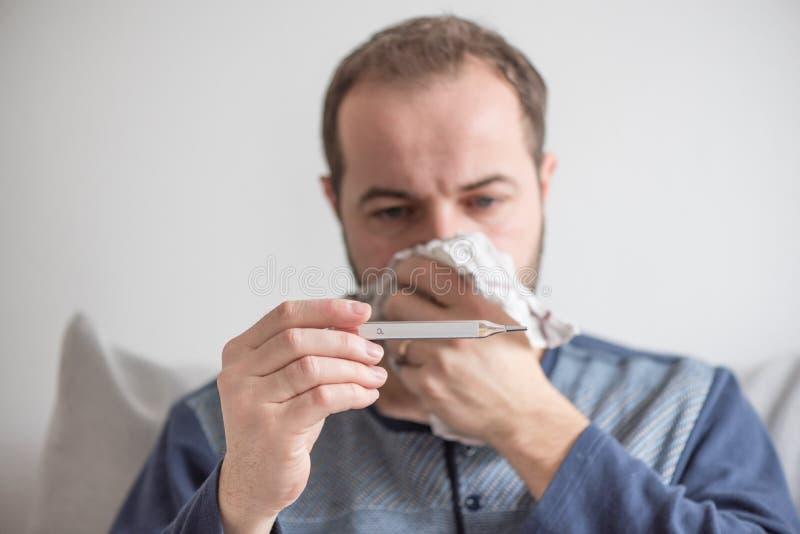O homem doente verifica a temperatura corporal com um termômetro de mercúrio Tema de doenças virais, gripe, frios fotografia de stock royalty free