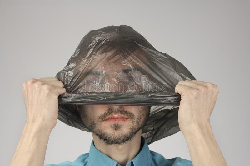O homem doentio com bordos rachados remove ou põe o saco de plástico preto de sua cabeça, fundo cinzento, problema grande da ecol fotos de stock