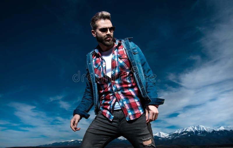 O homem dramático na roupa e nos óculos de sol das calças de brim levanta exterior imagem de stock