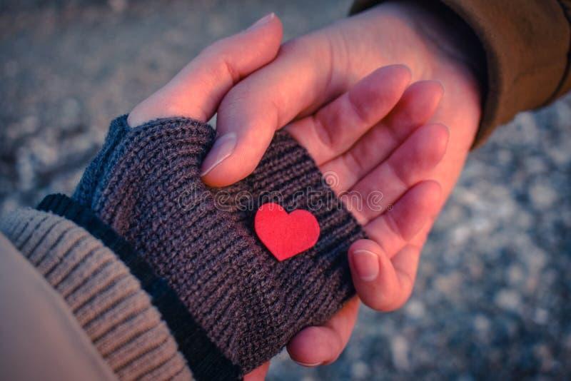 O homem e as mãos fêmeas guardam um coração vermelho pequeno na luz do por do sol foto de stock royalty free