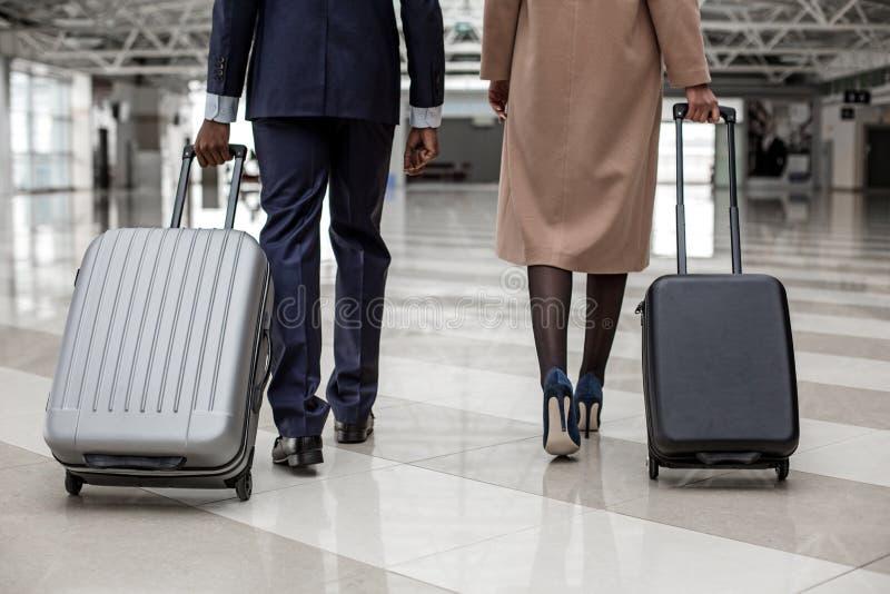 O homem e a fêmea estão andando no aeroporto com malas de viagem imagem de stock royalty free