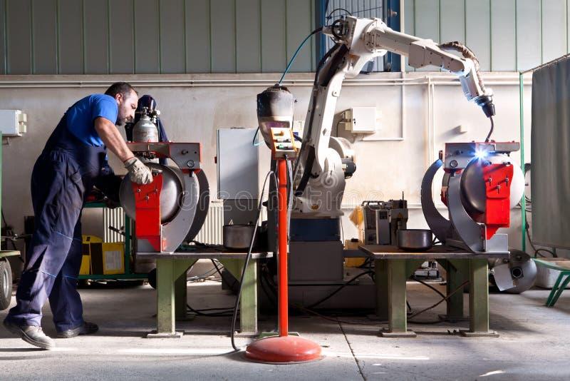 O homem e a máquina robótico trabalham junto dentro da construção industrial fotos de stock
