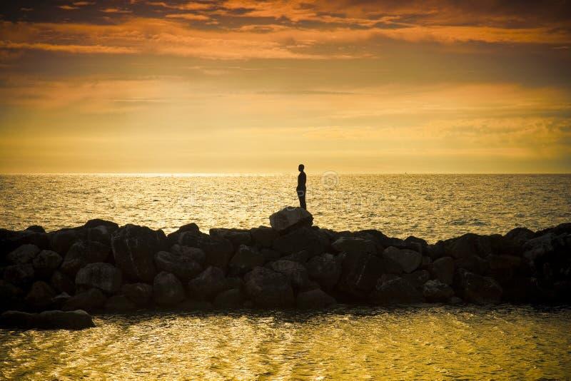 O homem e o mar no por do sol - imagem do conceito - fundo do estilo da silhueta fotos de stock royalty free